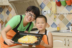 Mom and kid making pizza. Chinese mom and kid making pizza in kitchen together royalty free stock photos