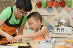 Mom and kid making pizza. Chinese mom and kid making pizza in kitchen together stock image