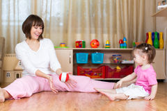 Mom and kid play with toy ball indoors Stock Images