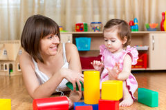 Mom and kid play toys indoors Stock Photo
