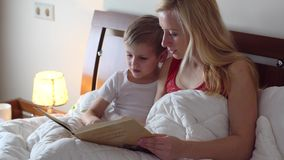 Mom with kid reading book stock video