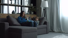 Mom and kid relaxing on couch with digital devices stock footage