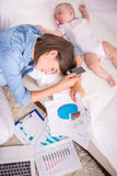 Mom and kid. Tired women falling asleep while working at home and her little baby is sleeping near Stock Image