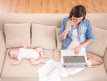 Mom and kid. Top view of young women is working at home while her little baby is sleeping Royalty Free Stock Photo