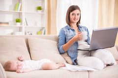 Mom and kid. Young women is working at home and drinking tea while her little baby is sleeping Royalty Free Stock Photo