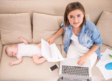 Mom and kid. Young women is working at home while her little baby is sleeping Royalty Free Stock Photo