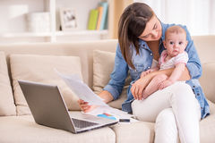 Mom and kid. Young women is working from home, holding baby girl on lap Stock Images