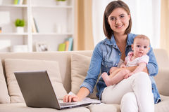 Mom and kid. Young women is working from home, holding baby girl on lap Stock Photo