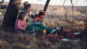 Mom and Kids Enjoying Warm Drink Under Tree. Full Length of Woman with Two Children Sitting Underneath Tree with Warm Beverage in Metal Thermos - Stopping to stock video