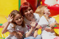 Mom and kids having fun on jumping castle. Young mother with her cute daughters waving you laughing on the bouncing castle outdoors in a bright sunny day. Happy Royalty Free Stock Photos