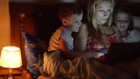 Mom with kids reading book. In bed stock video footage