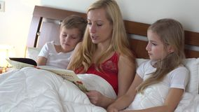 Mom with kids reading book stock video
