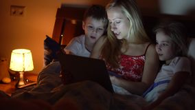 Mom with kids reading book. In bed stock video