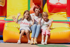 Mom & Kids Sitting On Bouncing Castle Stock Photography