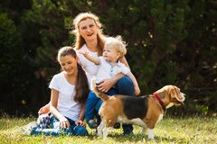 Mom with kids on a walk. Happy mother with her daughter, little son and beagle dog for a walk royalty free stock images