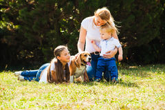 Mom with kids on a walk. Happy mother with her daughter, little son and beagle dog for a walk stock image