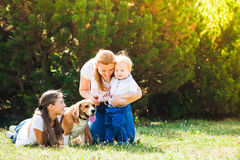 Mom with kids on a walk. Happy mother with her daughter, little son and beagle dog for a walk stock photography