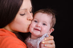 Mom kisses the baby of six months. Portrait of mother and baby at the hands of six mothers royalty free stock images