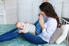 Mom kisses the bare feet of his son. Beautiful brunette woman,dressed in a white shirt and blue jeans,playing with his young son sitting on bed,baby with brown Royalty Free Stock Image