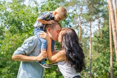 Mom kisses daddy who keeps their child. On their shoulders Royalty Free Stock Photo