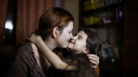 Mom kisses daughter hugging indoor woman and girl love friendship family stock footage