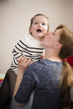Mom kisses a happy child Stock Image