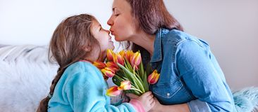 Mom kisses her daughter and hugs, sitting on the sofa in the room, happy family. Tulips as a gift for mother`s day. Woman with stock image