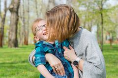 Mom kisses her little boy in the park in spring. Mom kisses her little boy in the park on the grass in spring stock photo