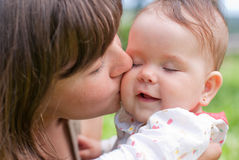 Mom kisses her little daughter, played Royalty Free Stock Photography