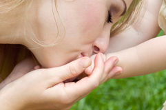 Mom kisses her little daughter's hands Royalty Free Stock Photography
