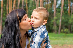 Mom kisses his little boy in the park Royalty Free Stock Images