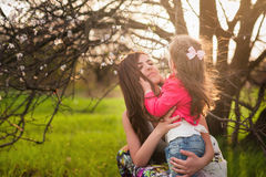 Mom kisses and hugs daughter on nature, family, motherhood, child Royalty Free Stock Photography