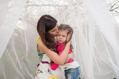 Mom kisses and hugs daughter on nature, family, motherhood, child Stock Photo