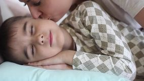 Mom kisses the little son while he sleeps. Beautiful Mom kisses a little son while he sleeps stock footage