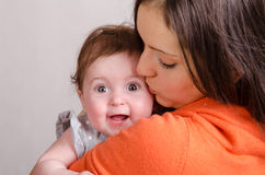 Mom kisses a six-month daughter. Portrait of mother and baby at the hands of six mothers royalty free stock photography