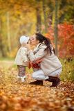 Mom kisses a small daughter in a spout, autumn park. Royalty Free Stock Photo