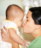 Mom kissing baby. Mom is kissing her little baby Royalty Free Stock Image