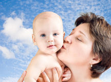 Mom kissing baby. 's cheek Stock Image