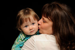 Mom kissing baby. Mother holding her son, giving him a kiss on the cheek Royalty Free Stock Images