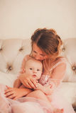 Mom kissing baby boy in bedroom Royalty Free Stock Photos