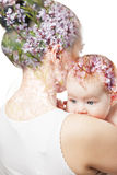 Mom kissing baby. Double exposure . mothers hugging baby on a background of beautiful flowers Royalty Free Stock Images