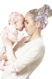 Mom kissing baby. Double exposure . mothers hugging baby on a background of beautiful flowers Stock Photo