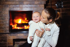 Mom kissing baby by the fireplace at home Stock Images