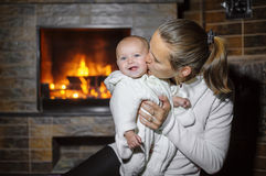 Mom kissing baby by the fireplace at home Royalty Free Stock Photos