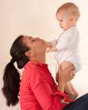 Mom kissing baby hand Stock Images