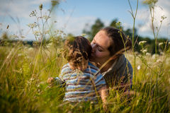 Mom kissing baby. On the meadow Royalty Free Stock Photography