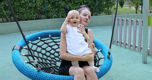 Mom kissing the cute baby boy on the swing stock video footage