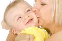 Mom kissing her baby boy. Portrait of a cute adorable little baby boy with his mom Royalty Free Stock Photo