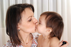 Mom kissing her daughter Stock Photo