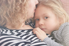 Mom kissing her daughter. Young mom kissing her little daughter on her forehead Stock Images
